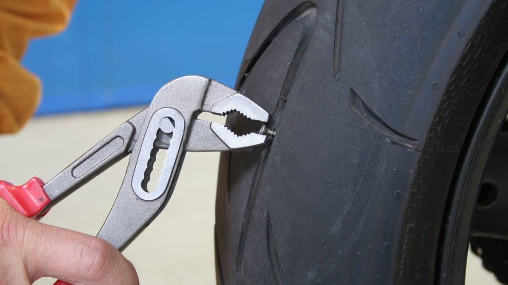 Schraube wird aus einem Motorradreifen entfernt