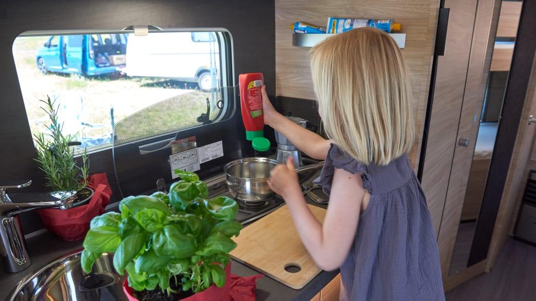 Mädchen kocht in der Küchenzeile des Knaus Südwind 500 QKD 60 Years