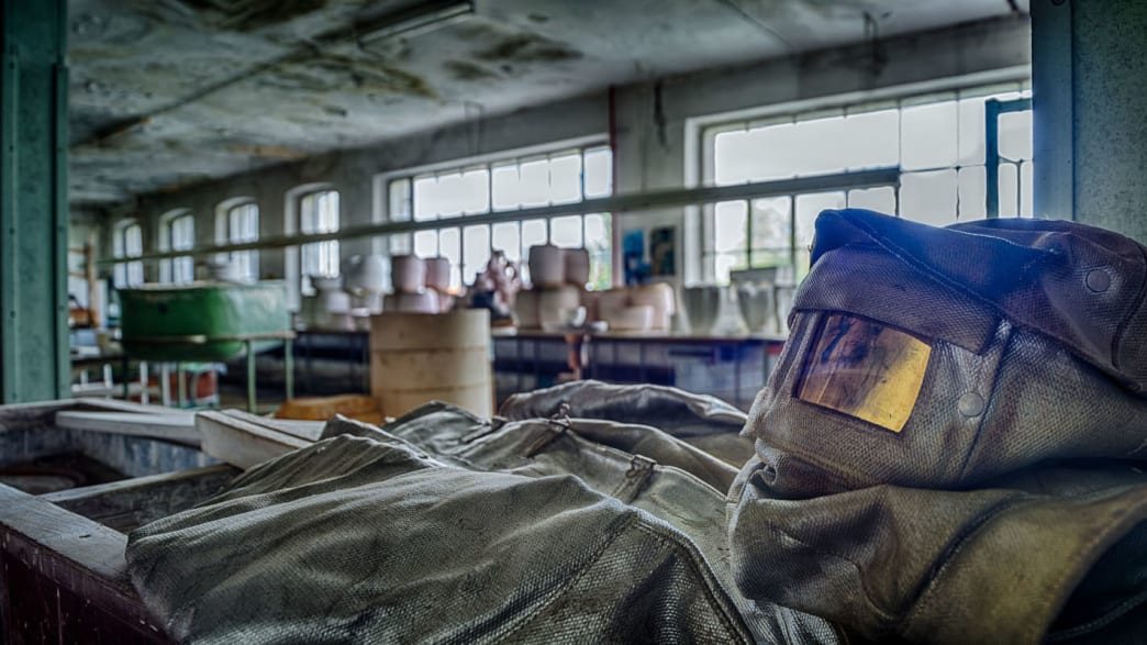 ein Schutzanzug mit Maske liegt am Boden einer verlassenen Porzellanfabrik