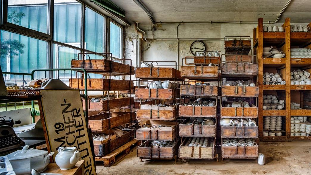 Holzregale mit Porzellan in einer verlassenen Porzellanfabrik