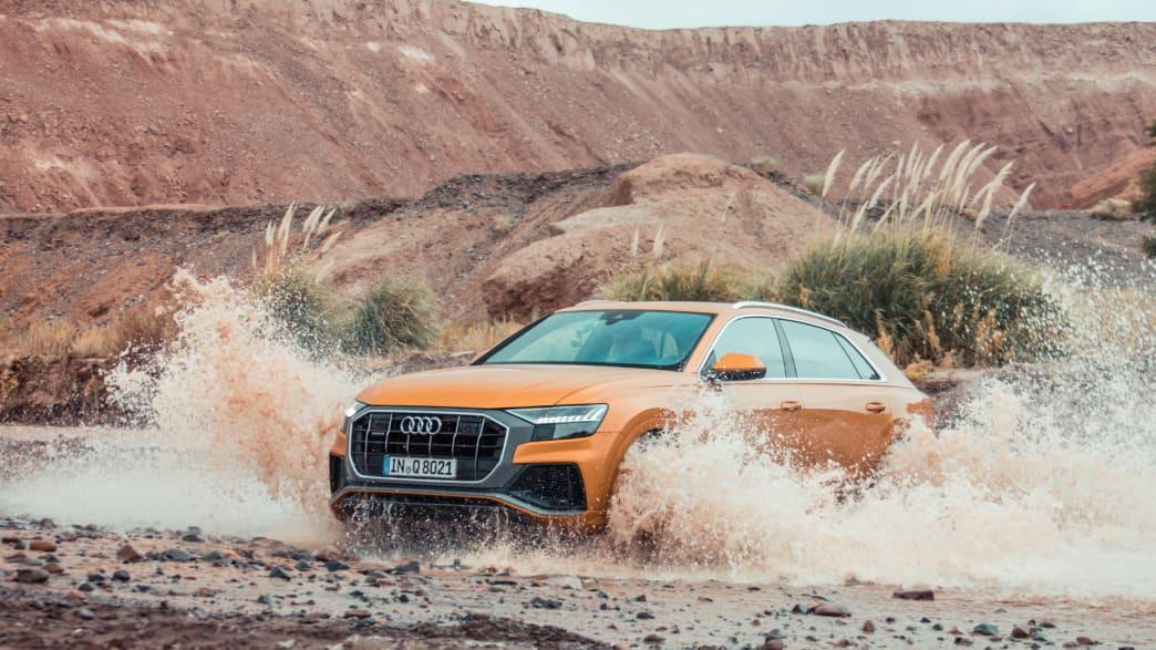 Ein Audi Q8 Coupe in Drachenorange fährt durch eine matschige Landschaft