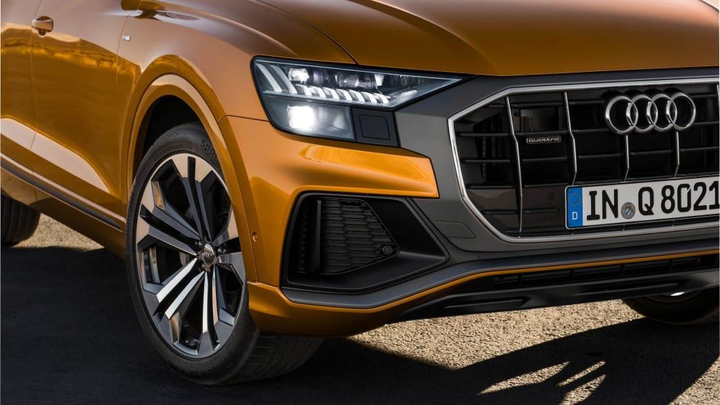 Die vorderen LED Scheinwerfer eines Audi Q8 Coupe in Drachenorange
