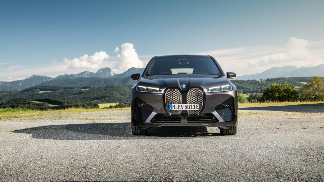 Der erste BMW iX in schwarz von vorn, parkend vor einer Bergkulisse