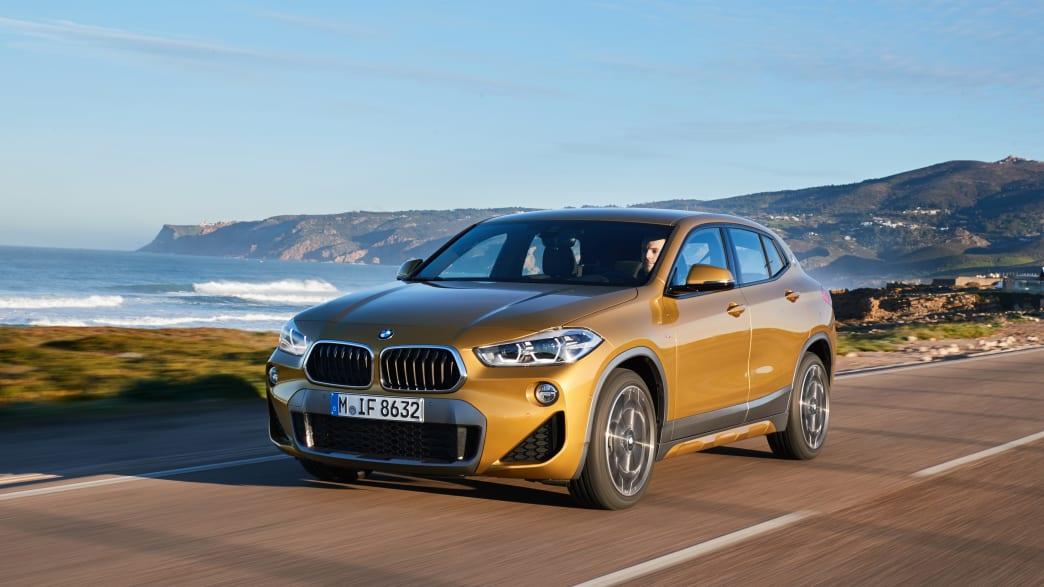 Goldener BMW X2 fährt eine Kuestenstrasse entlang