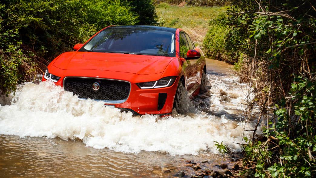 Roter Jaguar I-Pace faehrt durch Gelaende
