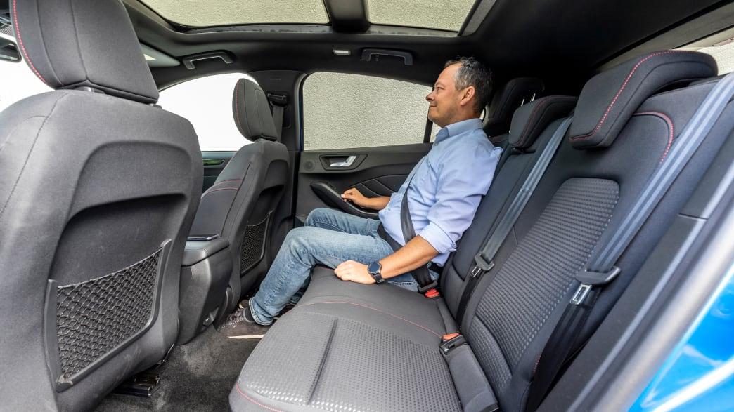 ADAC-Redakteur Jochen Wieler sitzt auf der Rueckbank eines Ford Focus Tunier