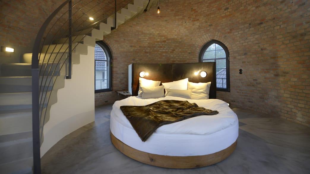 Ein Rundes Bett steht in einem Runden Raum mit einer Treppe