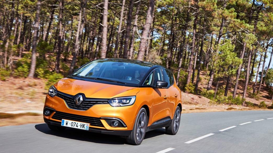 Ein orangener Renault Scenic Minivan fährt auf der Landstrasse