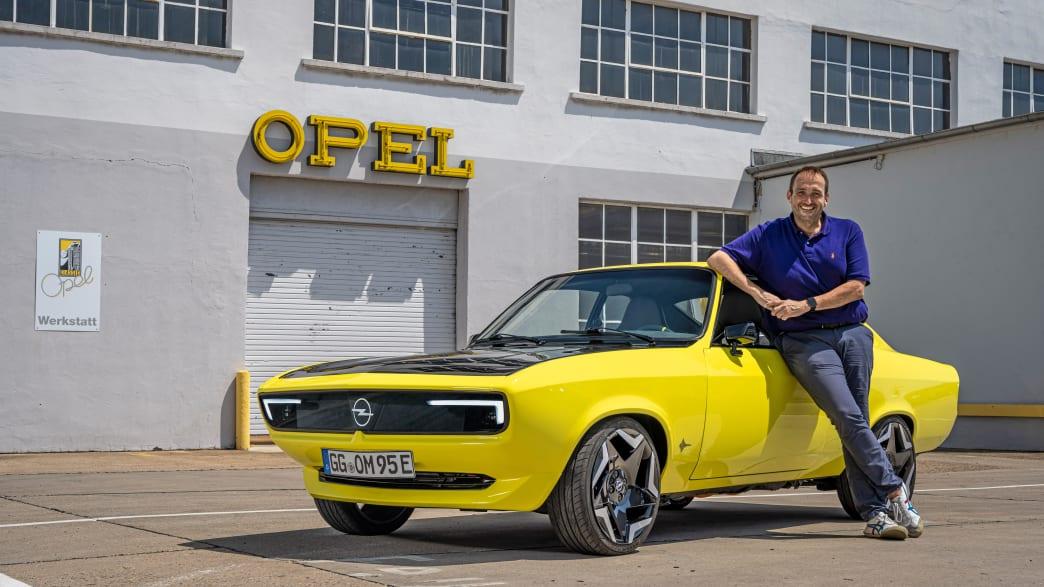 Ein Mann lehnt am Opel Mantra mit Elektroantrieb