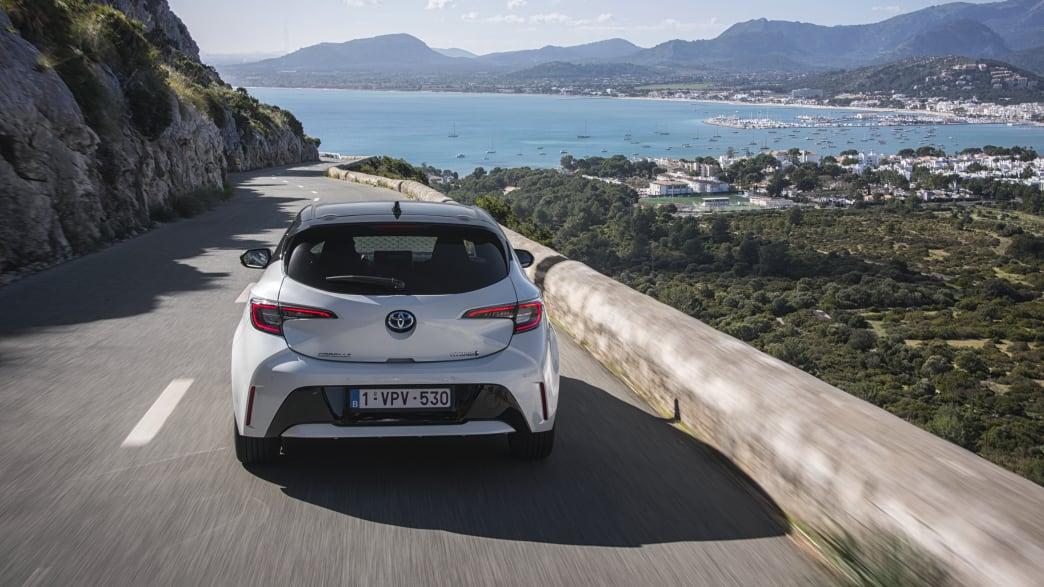 weisser Toyota Corolla fährt auf Strasse Front