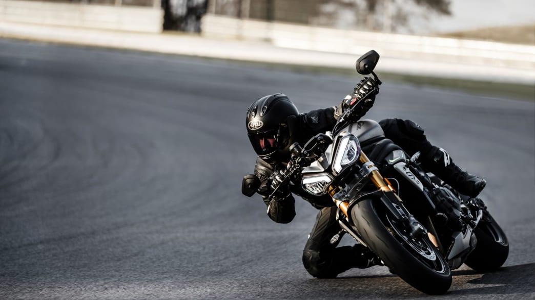 Ein Mann fährt auf dem Motorrad Triumph Speed Triple 1200 RS dynamisch durch eine Kurve.