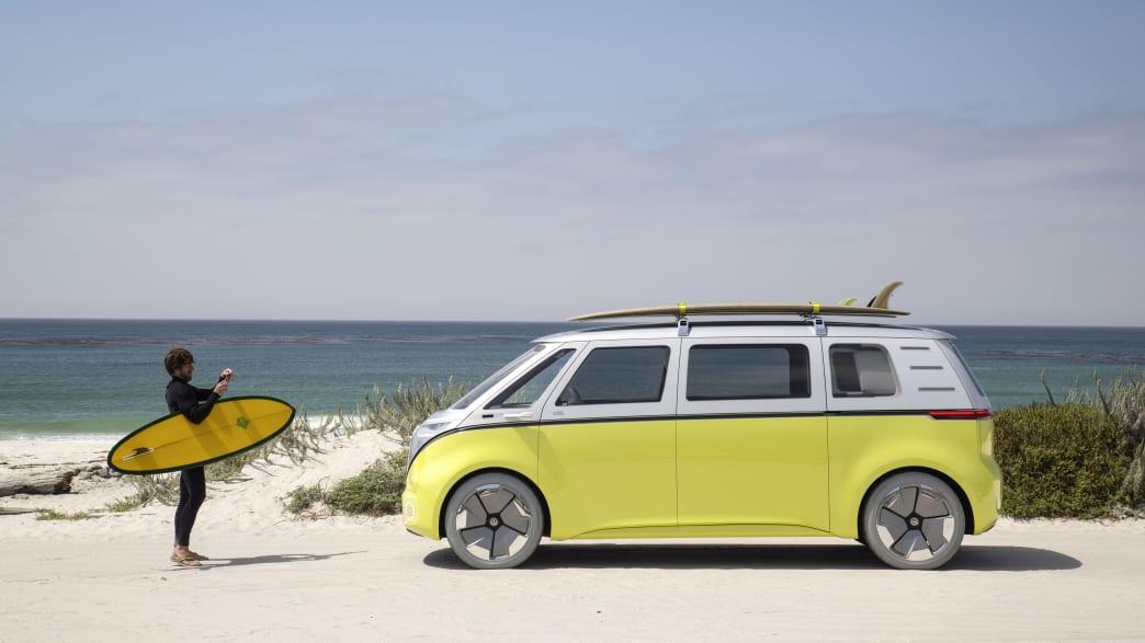 Ein Mann mit einem Surfbrett steht neben einem VW ID Buzz am Strand