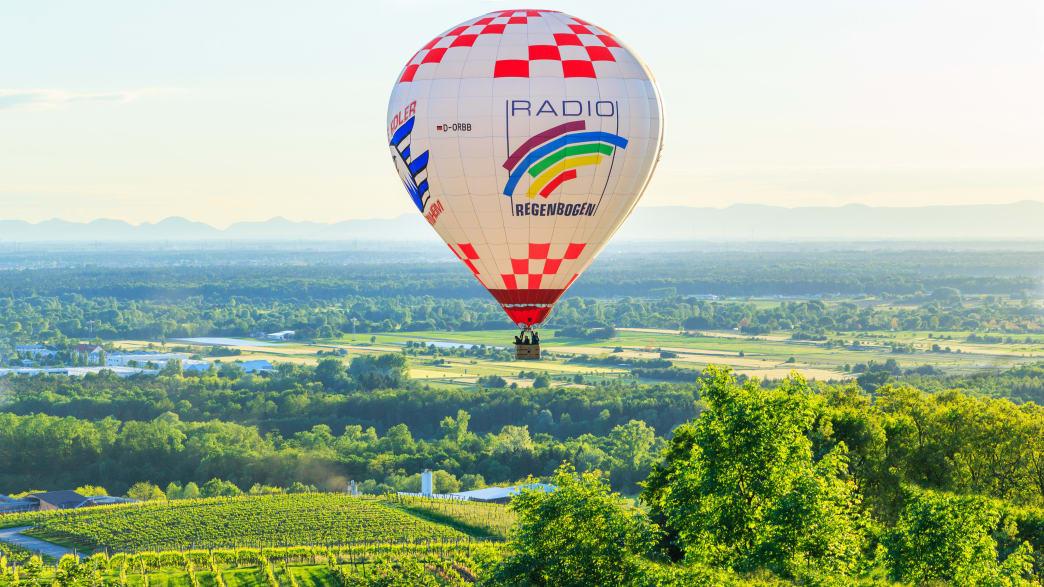 Ein bunter Heißluftballon fliegt über eine Landschaft mit Weinbergen
