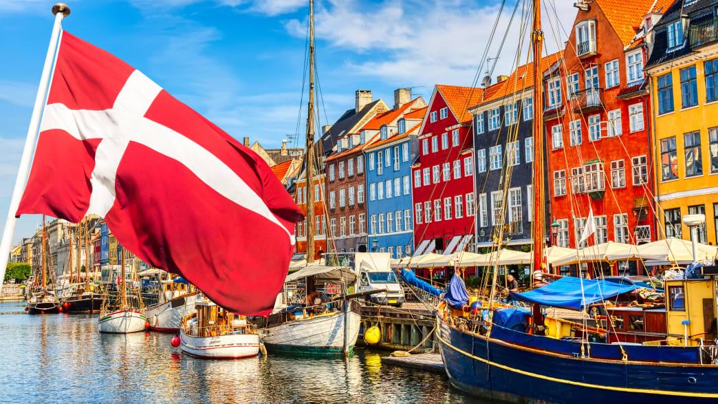 Eine Häuserzeile am Wasser in Koppenhagen mit Dänischer Flagge im Vordergrund