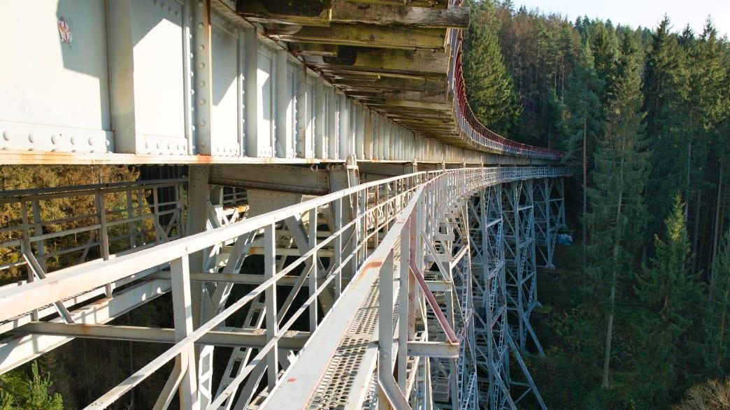 Ein Fußweg führt entlang einer Stahbrücke