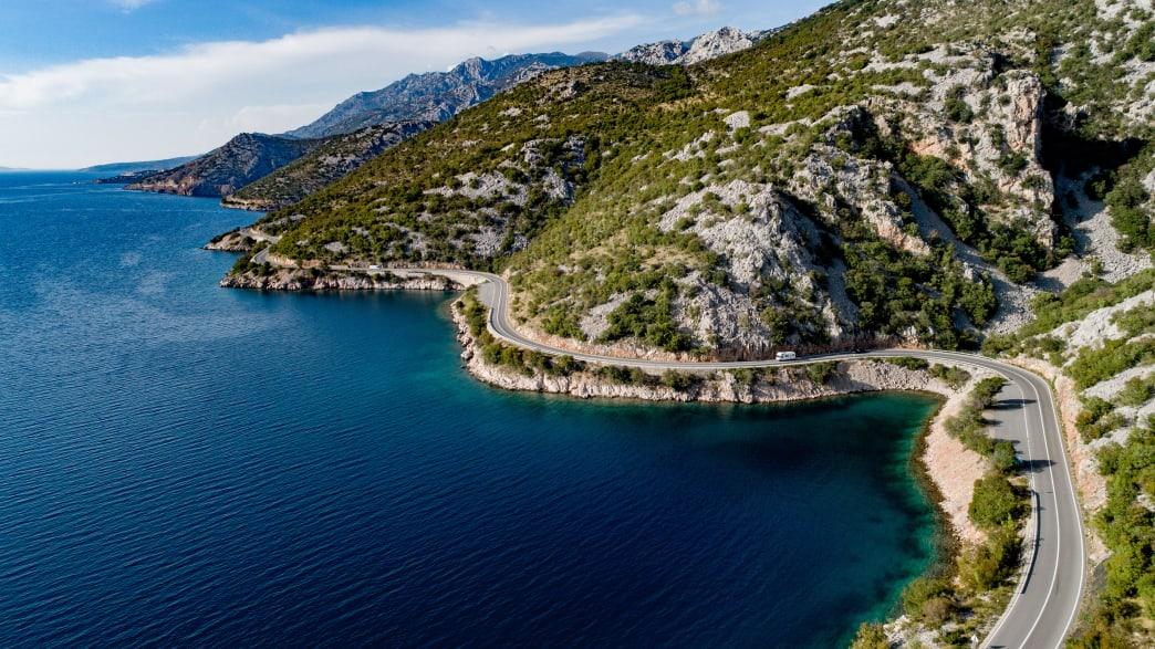 Eine Strasse führt direkt an der Küste Kroatiens entlang