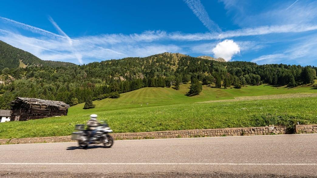 Ein Motorrad fährt durch die Bergwelt im Trentino