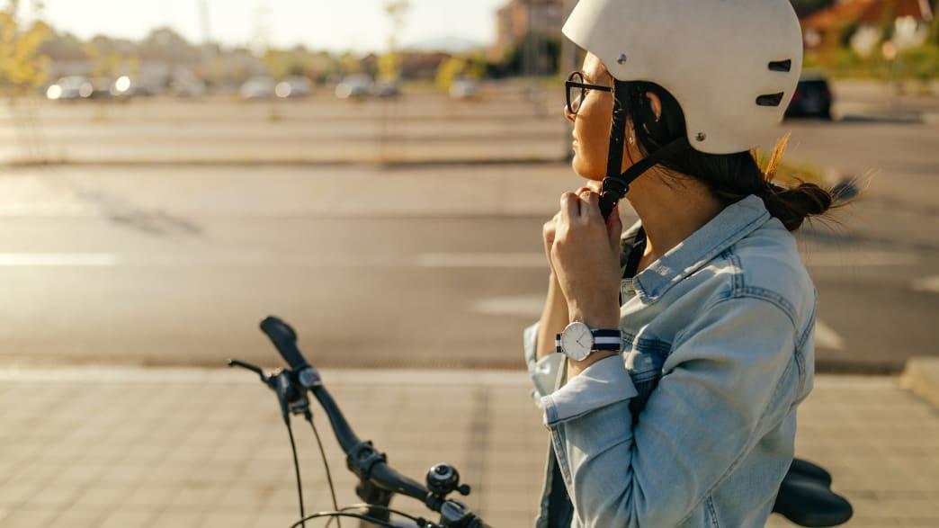 Frau schliesst den Gurt ihres Fahrradhelms