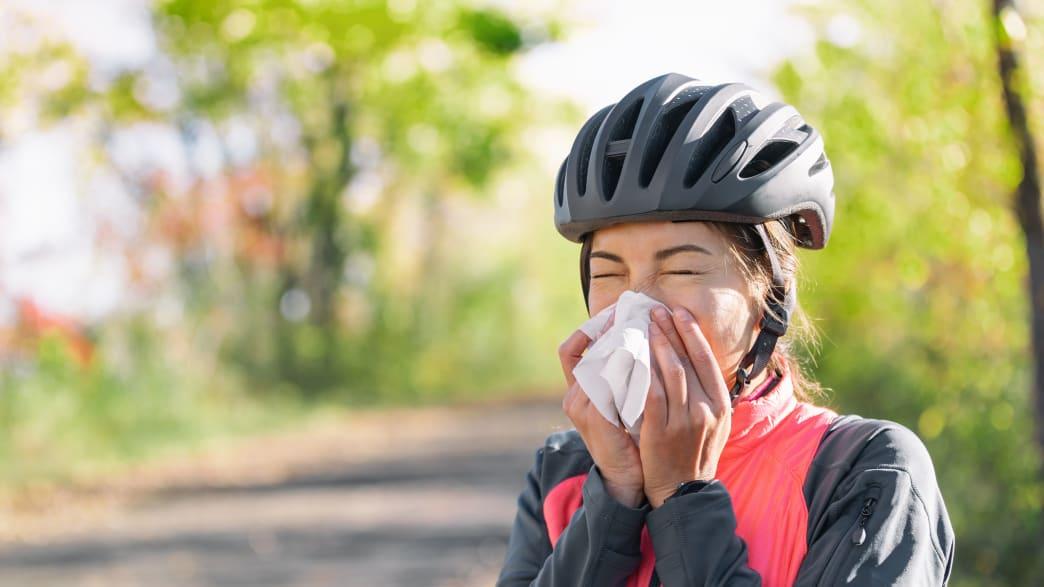 Radfahrerin schnäuzt in ein Taschentuch weil sie Schnupfen hat