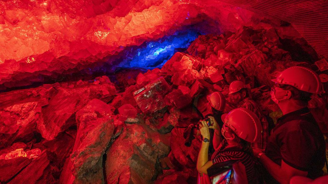 Zwei Menschen fotografieren rot angestrahltes Gestein in einem Bergwerk