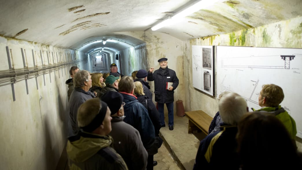 Menschen während einer Führung in einem Bunker auf Helgoland