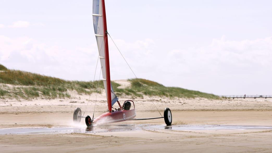 Ein Strandsegler fährt über den Sand