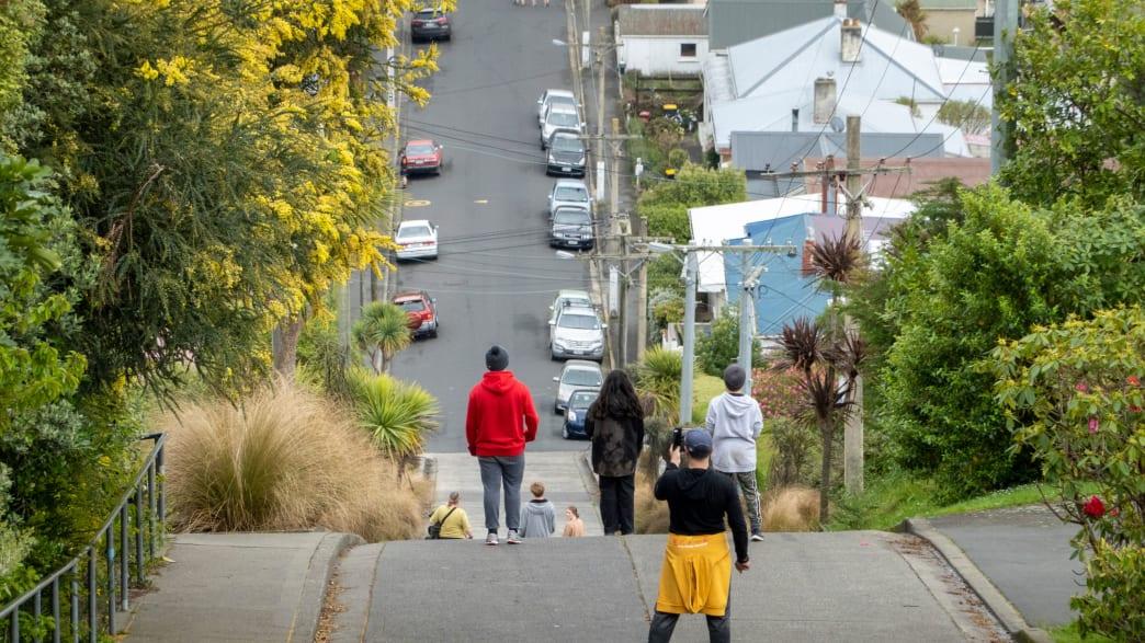 Touristen blicken die steile Baldwin Street in Dunedin New Zealand hinab und machen Fotos
