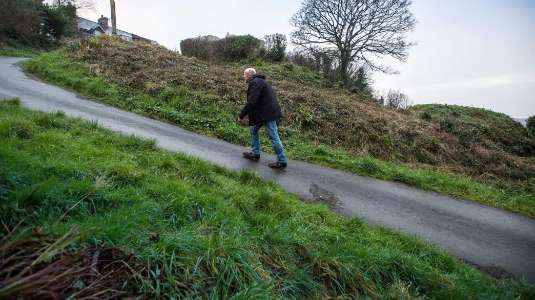 Ein Mann geht die steile Harlech Street in North Wales hinauf