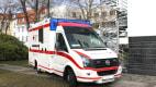 Ein Rettungswagen des Deutschen Roten Kreuzes steht in einer Wohnsiedlung