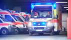 Ein Rettungswagen der Johanniter startet seine Fahrt mit Blaulicht aus einer Fahrzeughalle