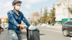 Radfahrer mit Mundschutz sitzt auf seinem Fahrrad