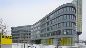 ADAC Zentrale von der Seite mit ADAC Logo im Vordergrund und verschneitem Gelände