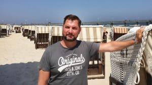 Mann steht zwischen Strandkörben am Strand von Usedom