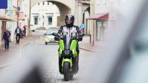 Ein E-Vespa Fahrer fährt mit Schutzkleidung auf einer Straße