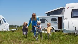 Kinder laufen mit einer Frau über eine Wiese vor einem Karavan.