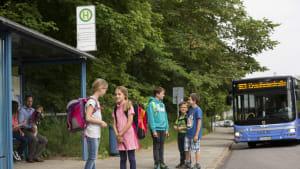Kinder stehen an einer Bushaltestelle und der Bus kommt.