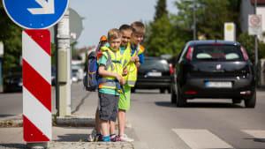 Schulkinder stehen an einem Zebrastreifen und schauen nach dem Verkehr