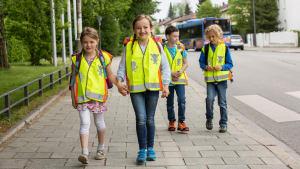 Schulkinder mit Warnweste auf dem Weg in die Schule