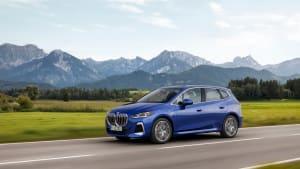 Ein blauer BMW 2er Active Tourer während der Fahrt vor Bergkulisse