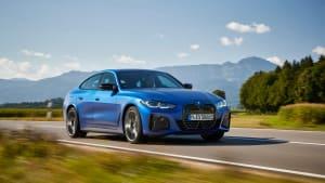 Der neue blaue BMW i40 M50 fahrend von der Seite auf einer Landstrasse in den Bergen