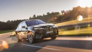 Der erste BMW iX in schwarz, während der Fahrt auf einer Landstraße