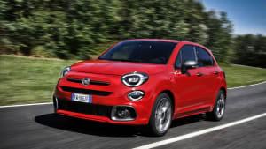 Ein roter Fiat 500 fährt dynamisch auf einer Landstrasse