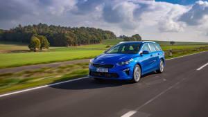 Blauer Kia Ceed Sportswagon faehrt auf Strasse durch Landschaft