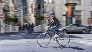 Eine Frau in Jeans, Lederjacke und mit Helm, fährt auf einem Herrenfahrrad durch die Stadt