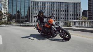 Eine Harley Davidson fährt auf einer Strasse, im Hintergrund stehen moderne Häuser