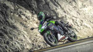 Ein Motorradfahrer auf einer Kawasaki Ninja 650 fährt dynamisch auf einer Strasse.