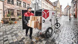 Paketzusteller liefert Pakete mit Lastenrad aus