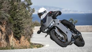 Das Motorrad Zero SR/S fährt auf einer Strasse durch eine Kurve