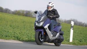 Ein Motorroller Maxsym 400 fährt auf einer Straße