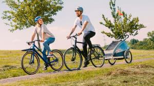 Paar auf Fahrrädern mit Kind im Fahrradanhänger